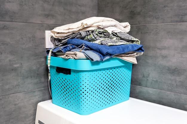 Ropa de cama doblada, jeans, toallas en una caja azul contra el borroso de un muro de hormigón gris