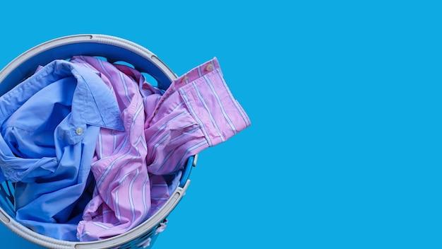 Ropa en una canasta de lavandería en azul. copia espacio