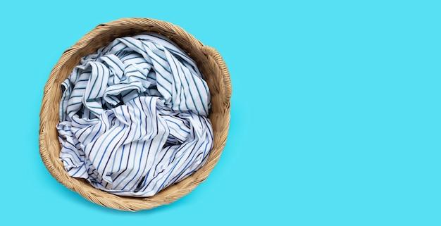 Ropa en canasta de lavandería sobre fondo azul. copia espacio