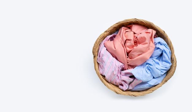 Ropa en canasta de lavandería sobre superficie blanca. copia espacio