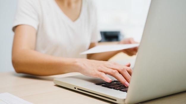 Ropa casual de la empresaria joven independiente de asia usando la computadora portátil que trabaja en la sala de estar en casa.
