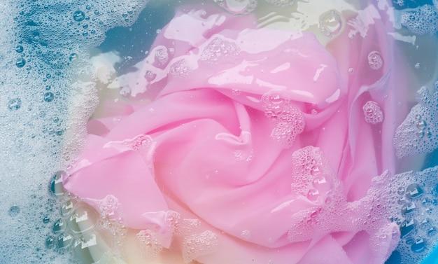 Ropa de color empapada en disolución de agua con detergente en polvo. concepto de lavandería