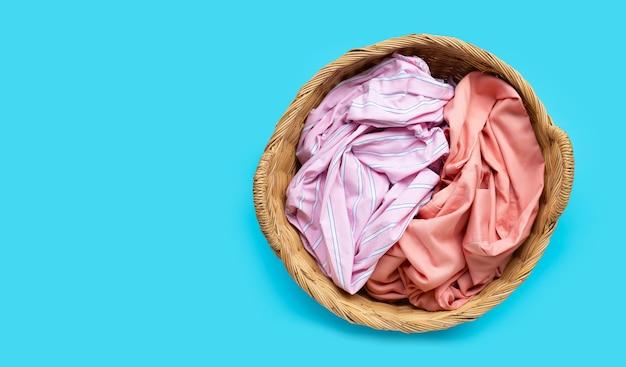 Ropa colorida en canasta de lavandería sobre fondo azul. copia espacio