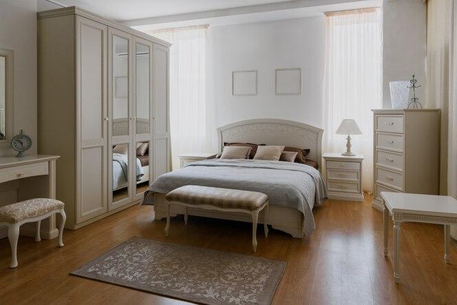 Ropa de cama clara en la habitación elegante con espejo