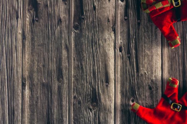 Ropa decorativa de duende navideño sobre fondo de madera. copie el espacio. enfoque selectivo.