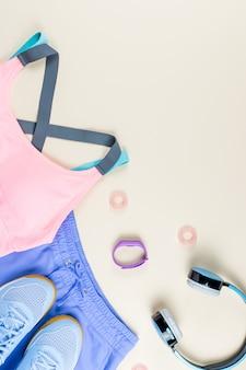 Ropa deportiva de mujer, zapatillas de deporte, auriculares y rastreador de fitness sobre fondo neutro. concepto de moda deportiva. lay flat