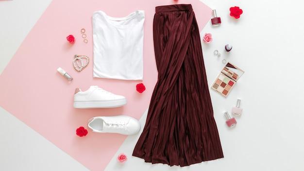 Ropa doblada para mujer moda urbana básica con accesorios flores maquillaje cosmética sobre fondo rosa.mujer primavera look verano traje falda zapatos zapatillas de deporte camiseta básica. banner web largo.
