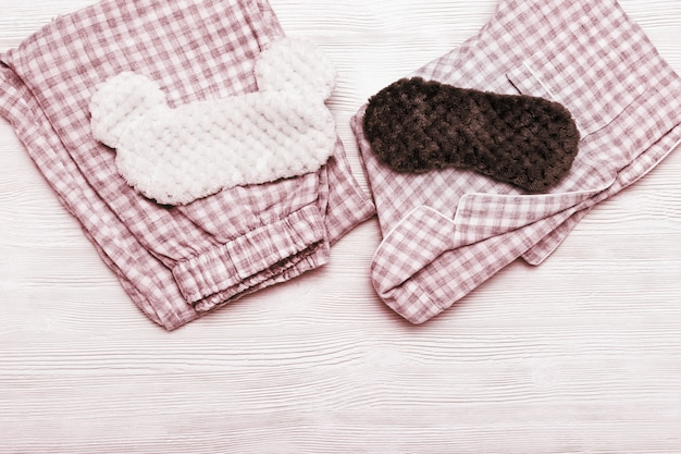 Ropa de dormir, pijama suave y cálido y máscara esponjosa sobre fondo blanco de madera con espacio de copia.