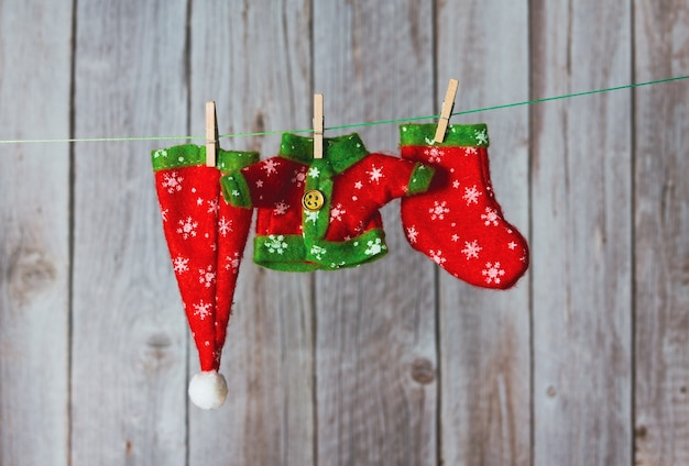 Ropa de duende navideño colgada con pinzas para la ropa. copie el espacio. enfoque selectivo.