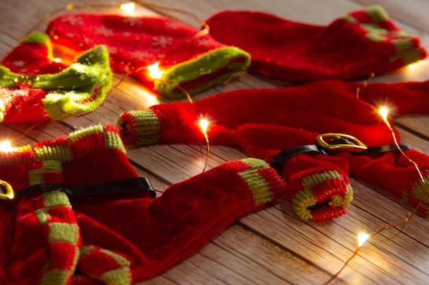 Ropa de duende navideño sobre fondo de madera con luces. enfoque selectivo.