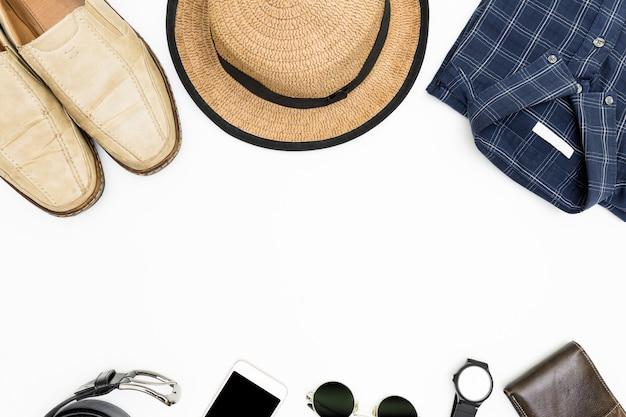 Ropa de hombre con zapatos marrones, camisa azul y gafas de sol sobre fondo blanco.