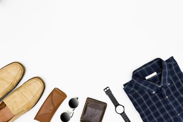 Ropa de hombre con zapatos marrones, camisa azul y lentes de sol en blanco.