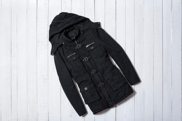Ropa de moda. abrigo de mujer negro con capucha sobre tablones de madera blanca