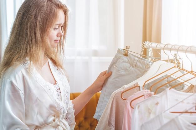 Ropa, moda, estilo y concepto de personas - mujer eligiendo ropa en casa vestuario