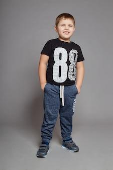 Ropa de moda del muchacho que presenta en fondo gris