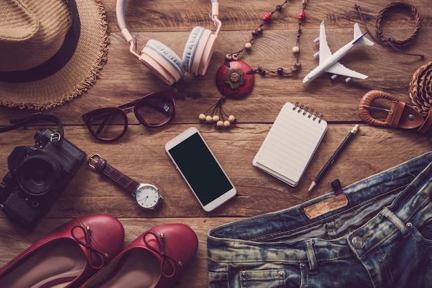 Ropa para mujer, colocada sobre un suelo de madera para viajar.