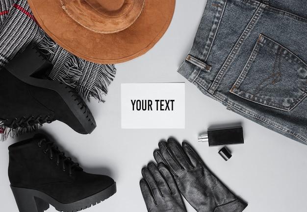Ropa de mujer de moda, zapatos, accesorios y papel blanco para su información sobre fondo gris. vista superior. copie el espacio. estilo plano