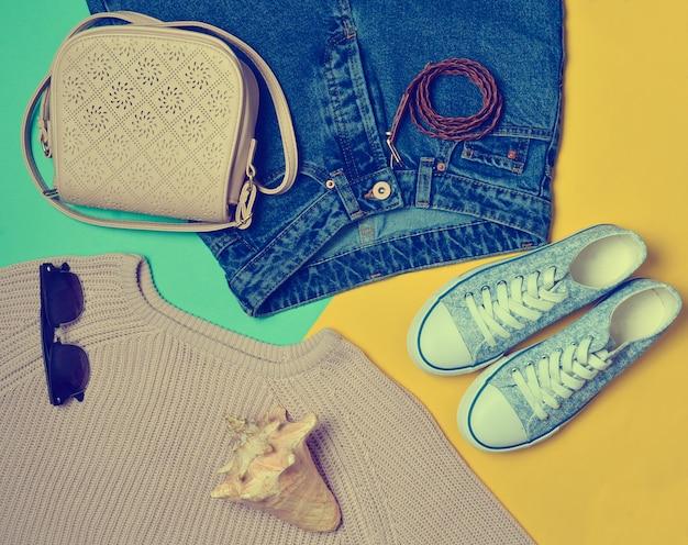 Ropa de mujer, zapatos y accesorios sobre fondo de color.