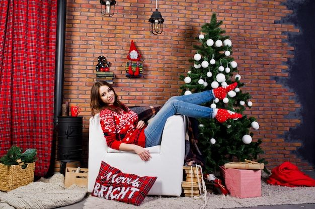 Ropa de niña en suéteres de invierno en la habitación con decoraciones de navidad.