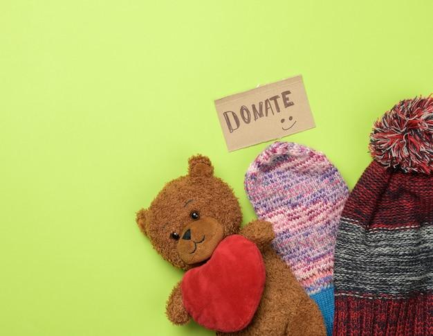 Ropa y oso de peluche marrón sobre un fondo verde, vista superior. donación de concepto