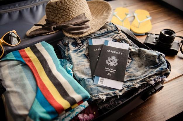 Ropa de pasaporte del viajero, billetera, gafas, dispositivos de teléfonos inteligentes, en un piso de madera en el equipaje listo para viajar.