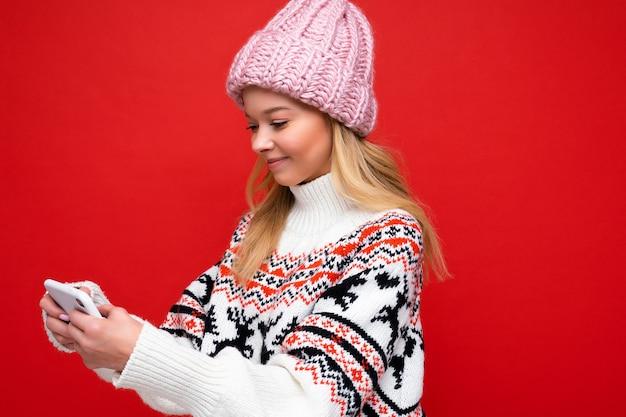 Ropa de pie aislado sobre fondo navegando en internet a través del teléfono mirando la pantalla del móvil.