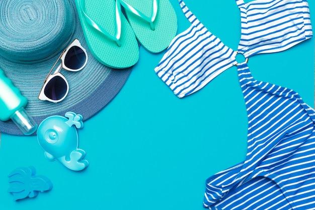Ropa de playa y accesorios sobre un fondo azul.