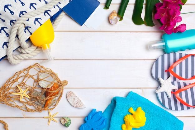Ropa de playa y accesorios sobre un fondo blanco de madera