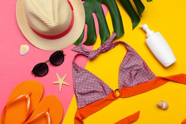 Ropa de playa y accesorios sobre fondo rosa y amarillo.