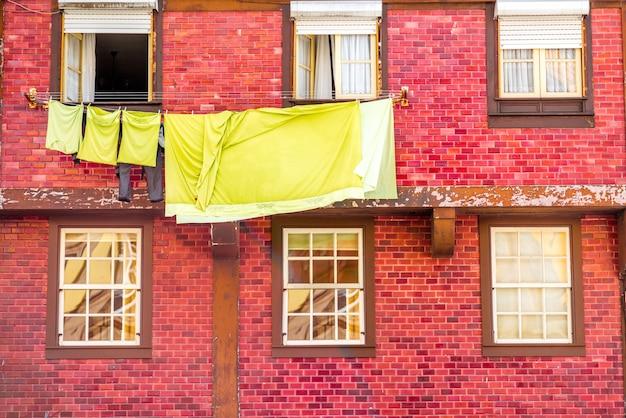 Ropa de secado en las ventanas del antiguo edificio rojo en la ciudad de porto, portugal