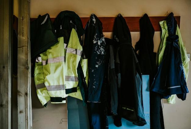 Ropa de trabajo abrigos y chaquetas colgando de un perchero.