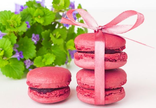 Rosa almendra dulce, postre de macarrones lila, pastel con bayas en blanco