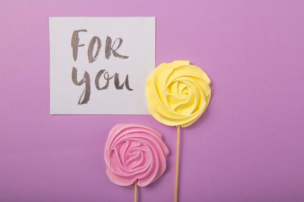 Rosa amarilla y rosa caramelo en colores pastel en un palo de madera con la tarjeta