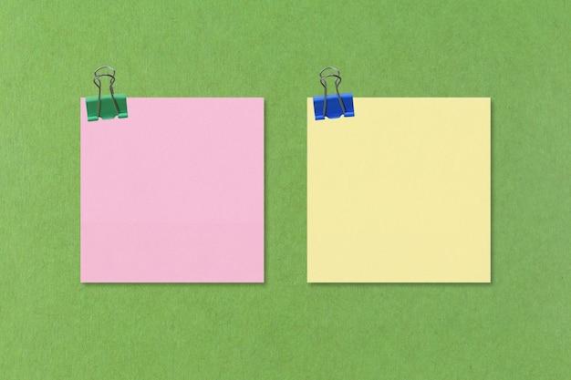 Rosa y amarillo de papel de nota en verde para diseñar en el trabajo.