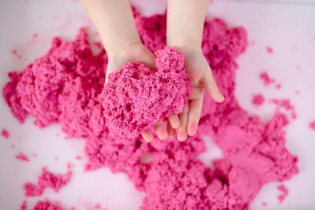 Rosa arena mágica en manos de un niño en un espacio en blanco de cerca. educación sensorial temprana. preparándose para la escuela. desarrollo