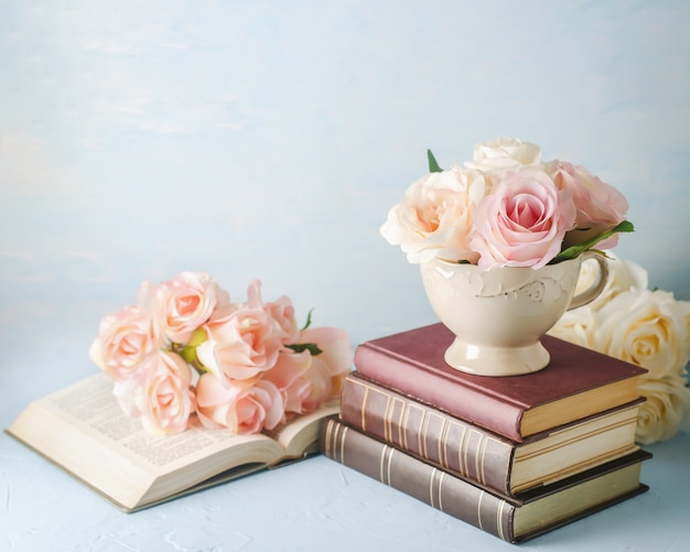 Rosa artificial rosa flores en copa vintage con libros en azul