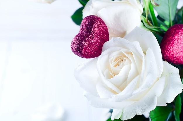 Rosa blanca y corazón rojo.