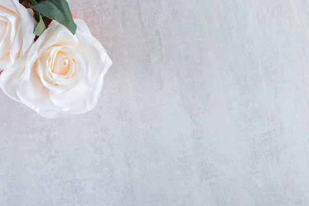 Rosa blanca en un cuenco, sobre la mesa blanca.