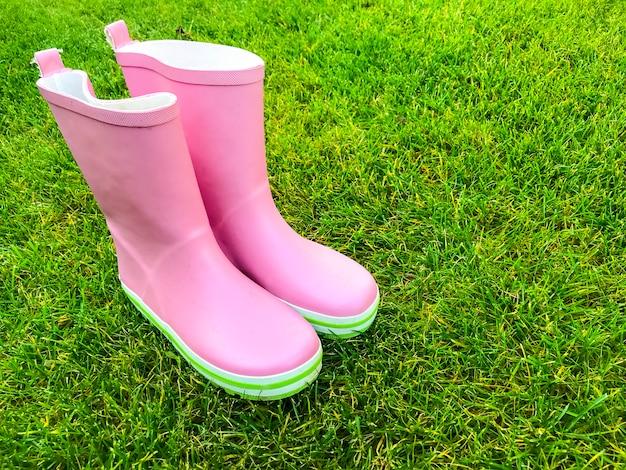 Rosa botas de goma de pie sobre la hierba verde.