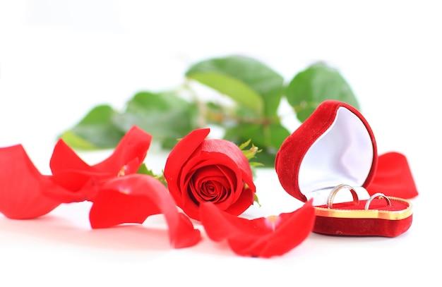 Una rosa y una caja con anillos.
