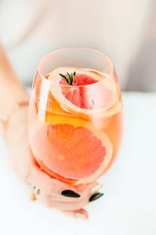 Rosa cócteles exóticos y frutas y mano femenina