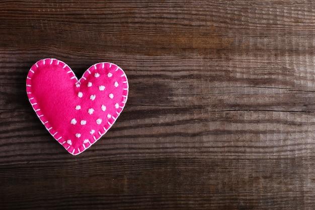 Rosa corazón hecho de fieltro sobre una mesa de madera