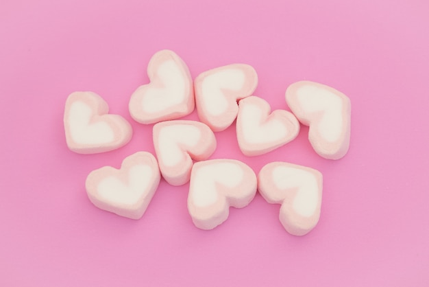 Rosa escuchar malvavisco, dulces corazones de malvavisco sobre fondo rosa