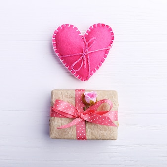 Rosa fieltro corazón y regalo hecho a mano sobre una mesa de madera blanca, concepto, banner, espacio de copia.