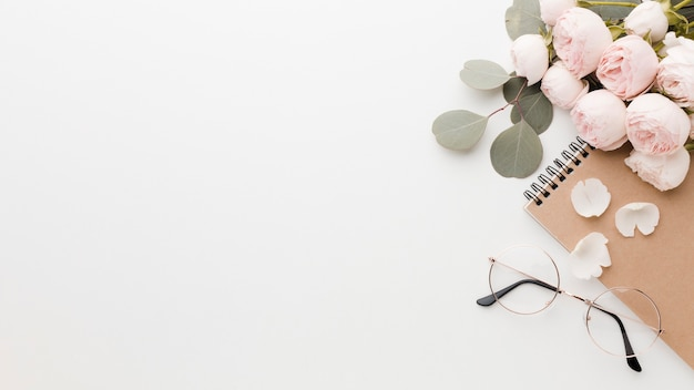 Rosa flores con arreglo de hojas con gafas y espacio de copia