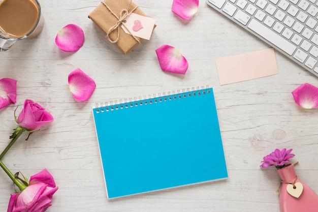 Rosa flores con caja de regalo y libreta en mesa