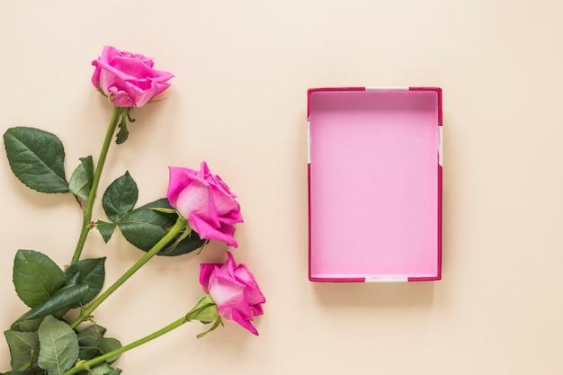 Rosa flores con caja vacía en mesa