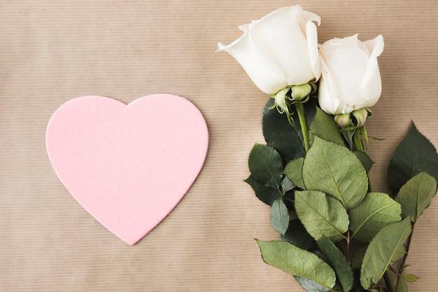 Rosa flores con corazón de papel rosa en la mesa