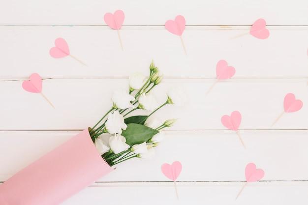 Rosa flores con corazones de papel en mesa