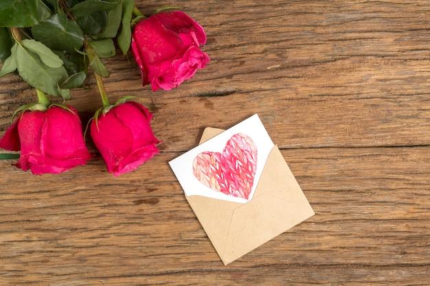 Rosa flores con dibujo de corazón en sobre